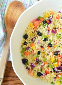 rainbow orzo salad with wooden serving spoon